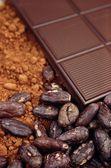 Bar of chocolate, cocoa beans , powder — Stock Photo