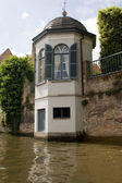 Brugge canal with white tower — Stock Photo