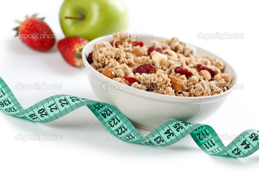 Bowl of muesli and measuring tape on white background — Stock Photo #2223594