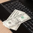 Dollar banknotes on laptop keyboard — Stock Photo