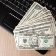 Foto Stock: Dollar banknotes on laptop keyboard