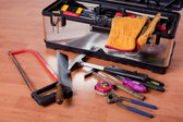 Tools in tool box on wooden floor — Stock Photo