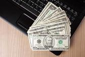 Billetes de dólar en el teclado del ordenador portátil — Foto de Stock