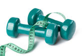 Green dumbell with measuring tape — Stock Photo