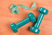 Green dumbells with measuring tape — Stock Photo