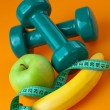 Dumbells with measuring tape and fruits — Stock Photo