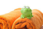 Orange towels and toy frog — Stock Photo