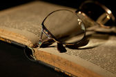 Detail of old book with glasses — Стоковое фото