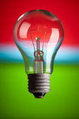 Light bulb on color background — Stock Photo
