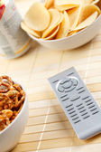 Remote control and salty snack — Stock Photo