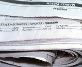 Newspaper stacked up and displaying what's featured inside — Stock Photo