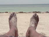 Beach - feet lounging in the sand — Stock Photo