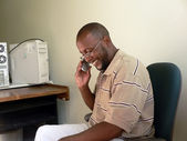 Man talking on cellphone at work — Stock Photo
