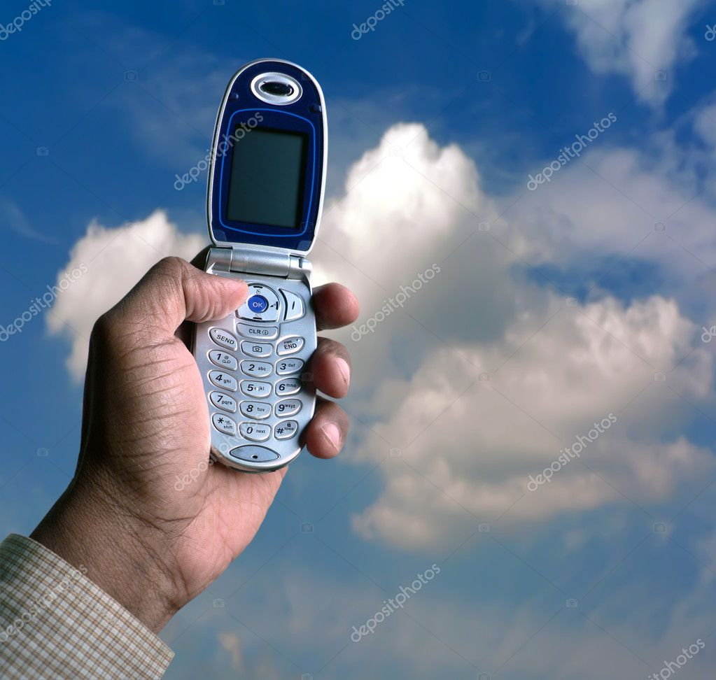 Photo of hand holding a cell phone up towards the blue sky — Photo #2387245