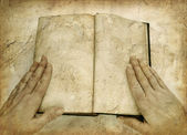 Grunge image of hands on open empty book — Stock Photo