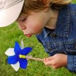 Boy blowing to pinwheel — Stock Photo