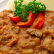 Pork goulash on white plate - Stock Photo