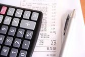 Calculator and bill and pen — Stock Photo