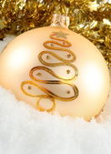 Gold Christmas ball digg in white snow — Stock Photo