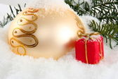 Gold Christmas bauble with red present — Stock Photo