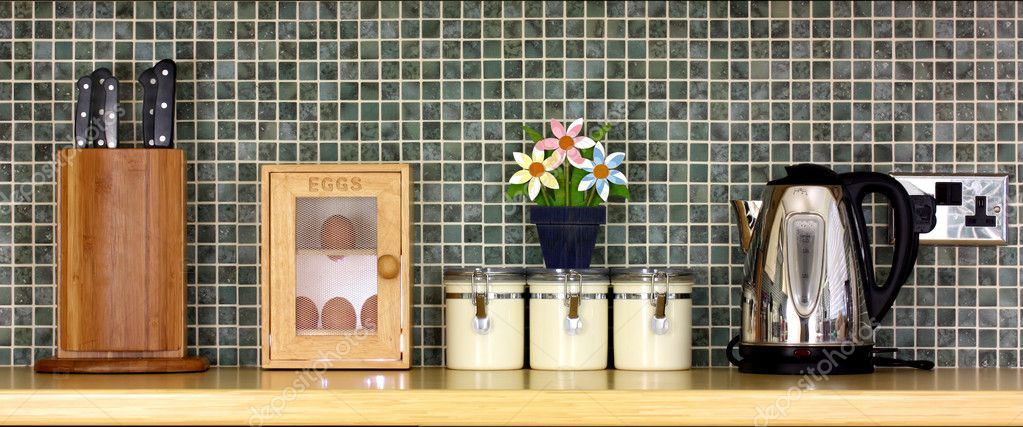 Tidy kitchen worktop with flowers against a tiled background — Stock Photo #2189898