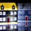 Two houses at night, one has lights on - Stock Photo