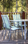 Chairs on decking in summer light — Stock Photo