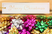 Merry Christmas with colourful bows — Stock Photo