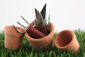Gardening tools in pots — Stock Photo