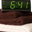 Stock Photo: Digital alarm clock on towels