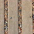 Stones in deckings gaps on beach — Stock Photo