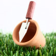 Plant pot with trowel on grass — Stock Photo