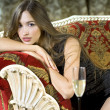 Rich woman on a red expensive sofa — Stockfoto