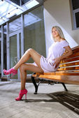Beautiful blonde woman on a bench — Stock Photo