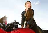 Young blonde on a big red motorcycle — Stock Photo