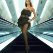 Woman on the escalator - Stock Photo