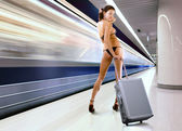 Beautiful woman with luggage in subway — Stock Photo