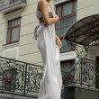 Brunette in long dress near a hotel — Stock Photo