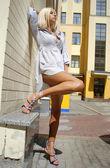 Vrouw staat in de buurt van huis muur en — Stockfoto