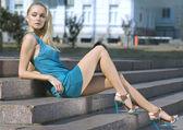 Sad blonde in turquoise dress — Stock Photo