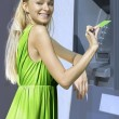 Blonde near a cash machine — Stock Photo