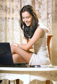 Girl with notebook computer at home — Stock Photo