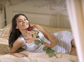 Girl with rose on the bed — 图库照片