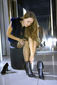 Woman fits on a boots in a boutique — Stock Photo