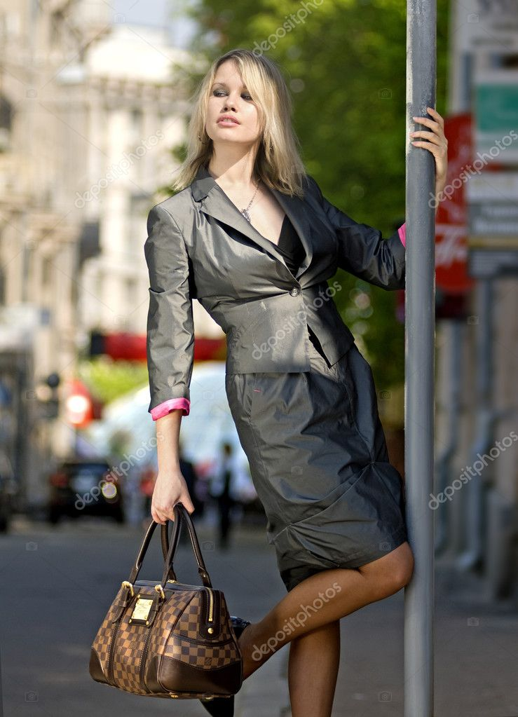 Flippant beautiful blond city woman stays on a street near bus stop — Stock Photo #2517047