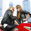 Two cheery motorcyclists and motorcycle - Stock Photo
