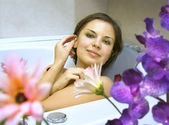 Woman in a bath with flower petals — Stock Photo