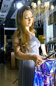 Woman chooses a dress in a boutique — Stock Photo