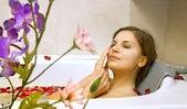 Mujer en un baño con pétalos de rosa — Foto de Stock
