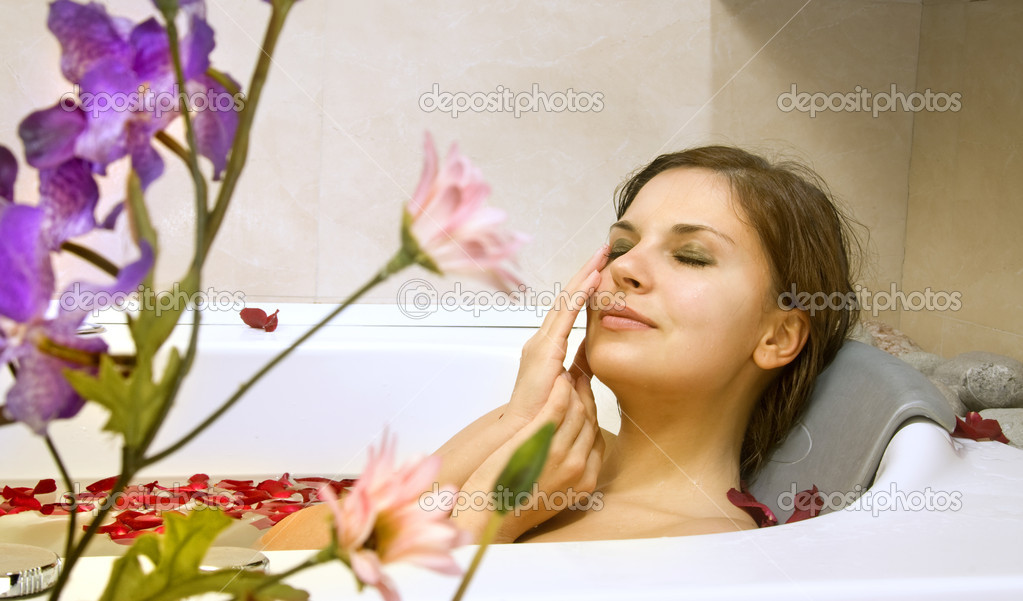 Beautiful woman in a bath with petals of rose — Stock Photo #2544548
